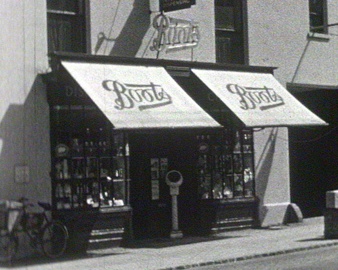 A still from [Sussex and Hampshire Scenes] (1930s) showing a 'Boots' shopfront