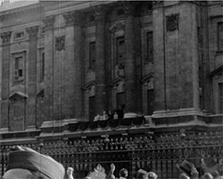 A black and white still image taken from TID 3419, showing the main balcony at Buckingham Palace as seen from street level outside the main gates. The Royal family are stood on the balcony waving to the members of the public that are gathered below.