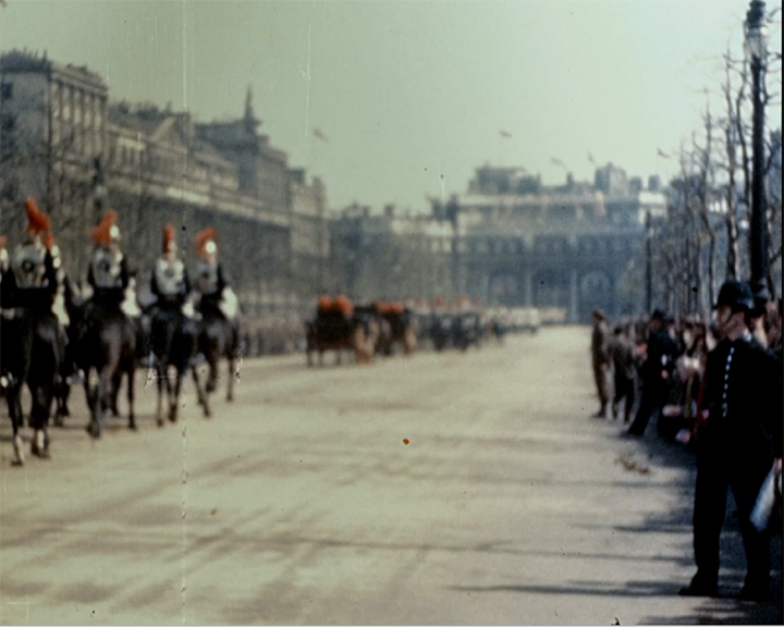 A colour still image taken from TID 3419, showing a view looking along The Mall towards Admiralty Arch, as a parade of mounted Household Cavalry guards process along the mall. A lone policeman stands on the road infant of the members of the public that have gathered to watch.