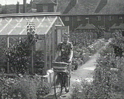 A still from [The Vegetable Gardens and War damage] (1940s) showing a Woman riding a bicycle
