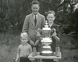 A still from [Jack Martin Pilot] (1937-1945?) showing a family group holding the FA Cup
