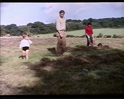 A colour still image taken from TID 3532, showing a group of family members, to adults and two young children in a field. A line of tall trees line the background. The woman is playing with a young child who is covered in dried grass.