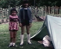 A colour still image taken from TID 3536, showing two girls standing outside a homemade makeshift tent in their garden. The two girls aged under 10 years stand smiling at the camera, the youngest has her arms folded in front of her chest.