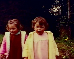 A colour still image taken from TID 3604, showing a close up image of two young children aged between 4 and 5 years old, walking through a woodland. One child wears a bright pink coat and the other in a bright yellow coat. Both children have neutral expressions on their faces.