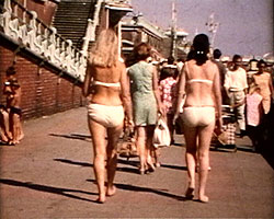 A still from 'Brighton Re-visited' (1969) - women in bikinis on the beach promenade