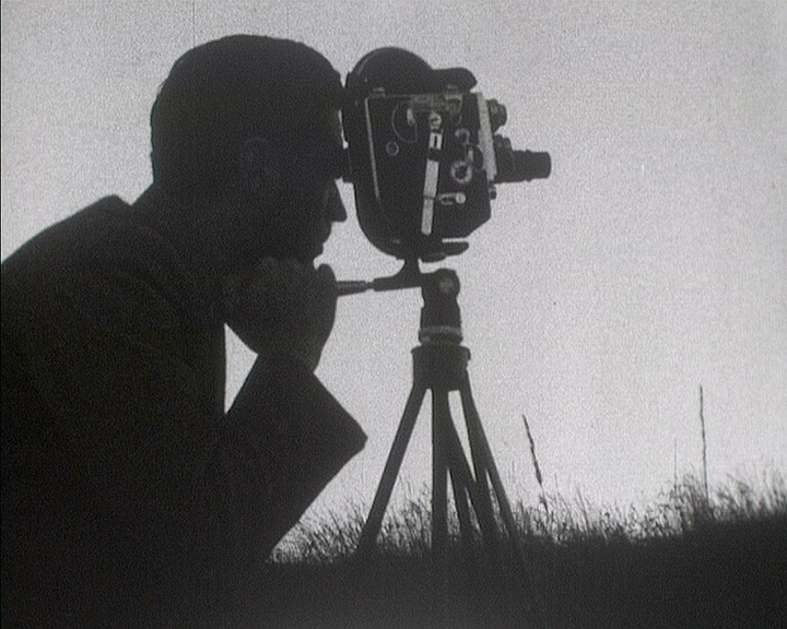 A still from Local News (1951) - a man with a cine camera