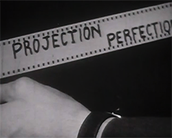 A black and white still image taken from TID 3758, showing the opening title of the production. The film maker stood in a projection booth, has written the words 'Projection Perfection' of approximately a foot and half of white 35mm leader in thick black capital lettering and is holding it up to the camera.