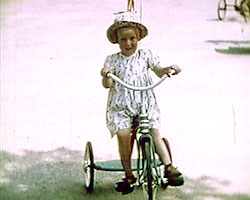 A still from 'A Garden of Beautiful Roses' (ca.1952) showing a girl on a tricycle