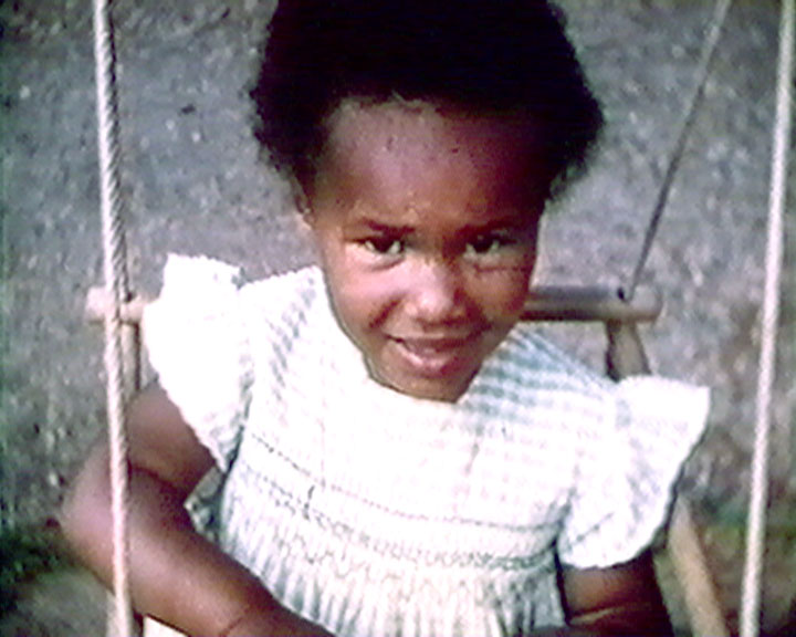A still from 'A Garden of Beautiful Roses' (ca.1952) showing a girl on a swing