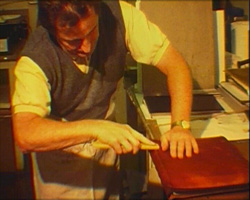 A still from 'Binding' (1997) - man demonstrating book binding