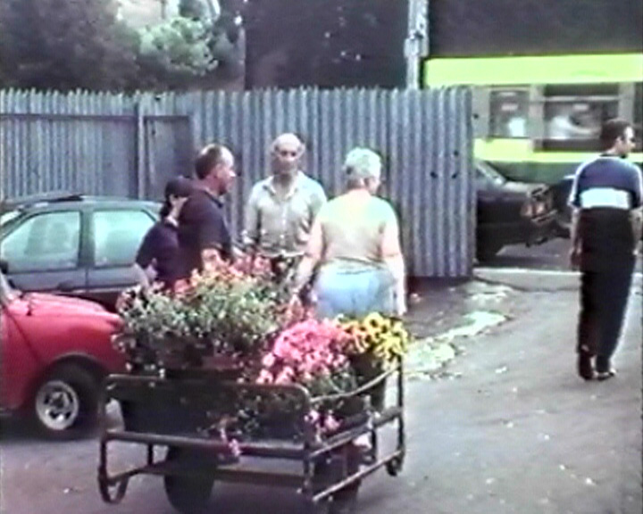 A still from 'Sevenoaks Cattle Market' (1999) - market stall holders with a flower cart