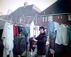 A still from [Local Scenes Eastbourne. Family Pictures] (1970s) showing Mrs Rose hanging out washing