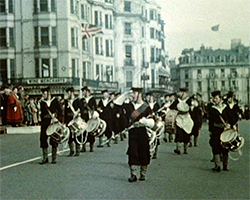 A colour still image taken from TID 448, showing a Naval military band in Sailor's uniform saluting to the dignitaries stood on a platform outside the Old Ship Hotel, as the forces troop process along the seafront.