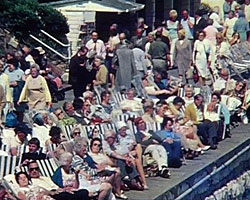 A still from 'Eastbourne - Sun trap and Showplace of the South' (1975) people in deckchairs on the sea front
