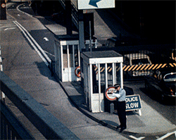 A still image from Victorian Story at Dover Docks (1980) showing a police man at a checkpoint  at Dover Hoverport slowing down the cars before they enter the British Rail Seaspeed hovercraft terminal area.}