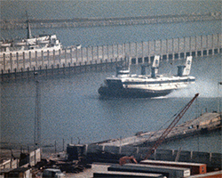 A still image from Victorian Story at Dover Docks (1980) showing a British Rail Seaspeed hovercraft coming into the Hoverport to collect or disembark passengers from the terminal building.}
