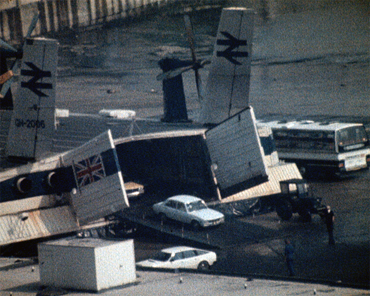 A colour still image from Victorian Story at Dover Docks (1980) showing cars driving off the Hovercraft and down the slipway toward the Hoverspeed terminal buildings.}