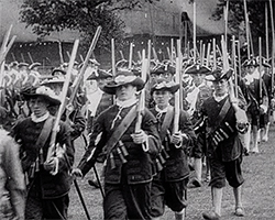 A black and white still image taken from TID 5082, showing a procession of men dressed in ca 1800's military dress holding pikes, short swords and early firearms, parading for a ceremonial event in Deal, Kent.