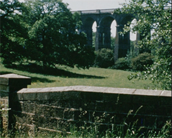 A colour still image taken from TID 5510, showing a ground level wide view of Balcombe Viaduct railway bridge as seen from below.