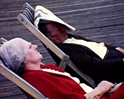A Still from Brighton Cocktail (1969) showing a couple sitting on deck chairs