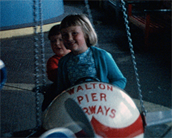 A still image from Frinton (1970) Showing a young girl and a boy on an airplane roundabout ride on Walton Pier. The plane they are sat in has the words Walton Pier Airways on its nose. The two children are smiling as the ride is in motion.}
