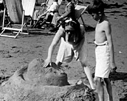 A Still from [Camping and Holidays] (1946 - 1949) showing members of the Dickins family on the beach at Broadstairs