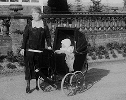 A black and white still image taken from Foxhunt Manor (1926) showing a woman wearing an Edwardian smock dress with white collar stood next to a baby in a Bonet in a large Edwardian pram. The group are outside the front of  Foxhunt Manor, by the ornamental banister style cast concrete railings.}