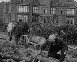 A black and white still image taken from \cf2 Wimbledon; Model Aeroplane; Farm; Tennis (ca.1930s) \cf0 showing a close up view of three men in flat caps and day suits from the Foxhunt estate staff working with a wooden horse drawn trailer, to load the logs and cut branches from a large felled tree within the estate grounds.}