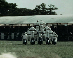 A colour still image taken from TID 6913, showing a motorcycle display team squad performing tricks and stunts in the outdoor arena at the Ardingly Show. Dressed in white clothing, the squad have formed a pyramid of drivers whilst in motion on their bikes.