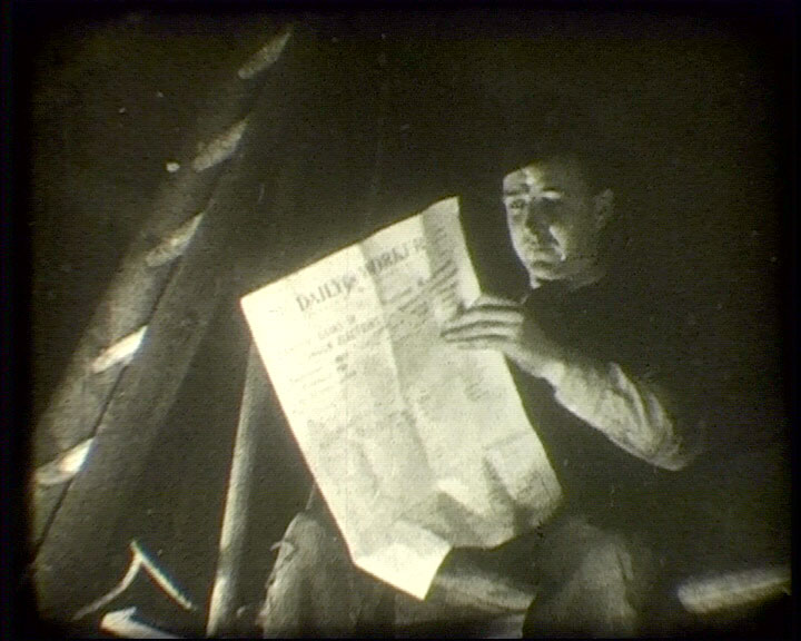 A still from [Advert for Daily Worker] (1938) showing a man reading a the Daily Worker newspaper