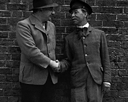 A still from TTID 7041 - Two Friends, (ca. 1950s) showing a black and white still image of two men dressed in a day suits and hats, shake hands whilst stood next to a wall, as they are being held at gun point by a firing squad of Prussian soldiers.