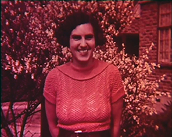 A magenta colour still image taken from TID 7487, showing a portrait image of Doris Lauste dressed in a cowl neck short-sleeved top, looking at the camera and smiling. Behind her in the garden border are a group of Yellow and pink flowering trees.