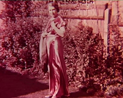 A magenta colour still image taken from TID 7488, showing a full length portrait shot of Bessie Lauste stood in the back garden of her home, wearing a long length satin evening dress and holding a fox fur stole in her right hand. She has a neutral expression on her face.