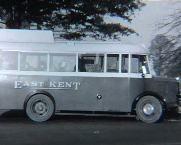 A black and white still image taken from TID 7491, showing the side of a two toned livery East Kent bus. The bus is a single decker with the words East Kent sign written on the lower third, towards the rear of the vehicle.