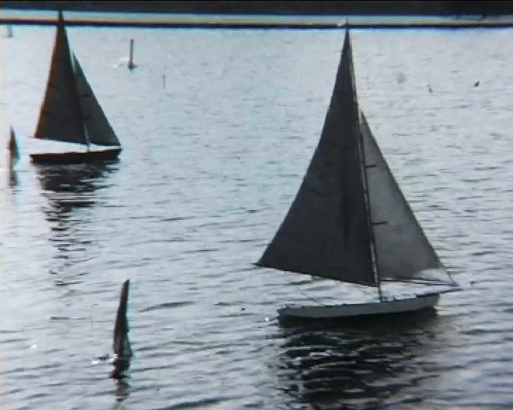 A black and white still image taken from TID 7491, showing a group of model sailing boats on a lake or boating pond.