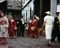 A colour still image taken from TID 7492, showing the film maker documenting the gathering of tourists and locals dressed in traditional clothing stood outside the Monte Railway Station entrance in Funchal, Madeira (Portugal).