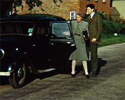 A colour still image taken from TID 7493, showing Alva Lauste opening a car door for a woman aged in her seventies, to exit the vehicle. The woman is dressed in a green-brown two piece dress suit holding a small dark coloured handbag. Alva is dressed in a mixed green-brown suit jacket and dark coloured trousers, looking at the woman with a neutral expression on his face.