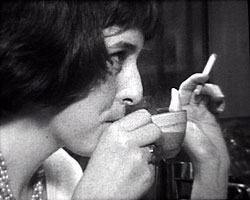 A still from 'A View of the Wells' (ca.1960) - a woman drinking coffee