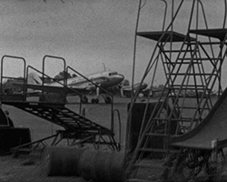 A black and white still image taken from TID 8098, showing the nose section of a commercial aircraft on an open runway, as seen through a stack of metal aircraft platform ladders in the foreground.
