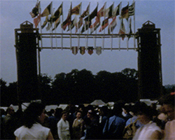 A colour still image taken from TID 940, showing the towered grand entranceway in to the main park for the Girl Guides Centenary event. Flags adorn the top of the entranceway, as crowds of girls and women are gathered, making their way inside the camp area.