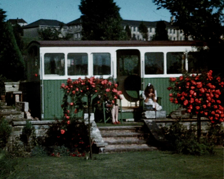A colour still image taken from TID 9490, showing a repurposed railway carriage being used as a garden summer house. The carriage has been painted in green and white with the entrance framed by flowering shrubs and plants. Outside, a woman and a teenage girl are sat relaxing in the sunshine on matching painted wooden chairs.