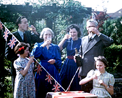A colour family portrait style still image taken from TID 9490, showing 6 members of a family dressed in their best clothing, together in the garden. The family are holding glasses of alcohol or punch as a toast to VE Day. Union flag bunting adorns the table at the front of the image in a 'V' shape.