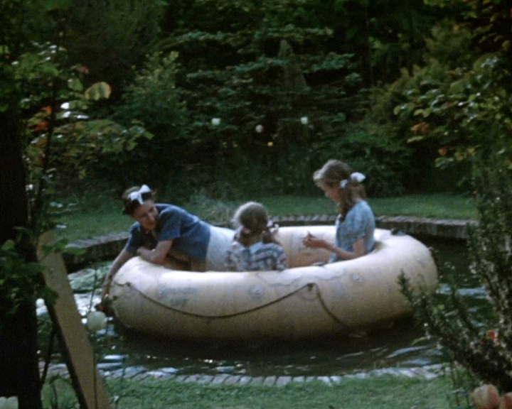 A colour still image taken from TID 9490, showing three girls aged between 10 and 14 years old wearing cardigans and summer dresses, sat inside a very large inflatable rubber ring or dinghy on a pond in a garden. One of the older girls is bending over the side of the ring to reach the edge of the pond. A large border of mature shrubs can bee seen in the background behind them.