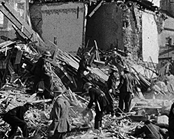 A black and white still image taken from TID 9497, showing a group of men dressed in A.R.P uniforms clearing through the rubble of bombed out buildings in Brighton. Piles of debris swamps the road and pavement, as what remains of the building can be seen behind them; brickwork and inner rooms now exposed.