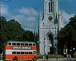 A colour still image taken from TID 9500, showing a red and white bus outside St Peter's Church Brighton, on the corner of St Peter's Place and London Road. The Clock and tower of the church visible from behind a row of trees.