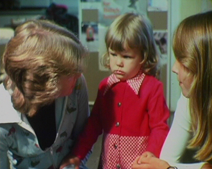 A Still from 'Childcare' (1977?) showing a child with two childcare students
